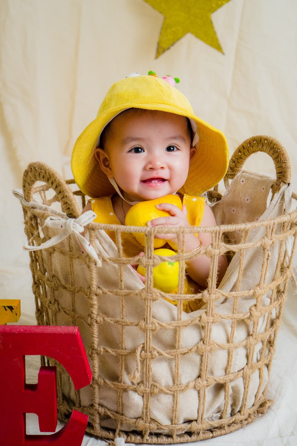 baby first teeth smiling in a basket wearing a yellow hat and yellow cloth holding yellow balls